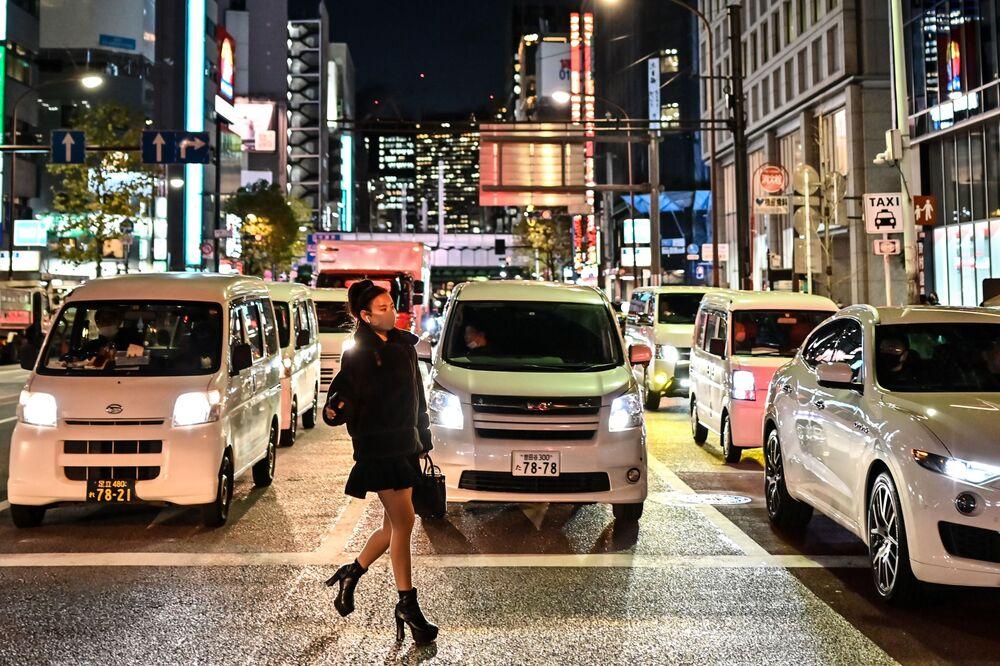 Una donna in mascherina attraversa una strada a Tokyo, Giappone, il 16 Dicembre 2020.