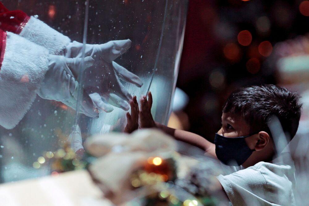 Un bambino comunica con il Babbo Natale attraverso uno schermo protettivo in un centro commerciale in Brasile, il 15 Dicembre 2020.