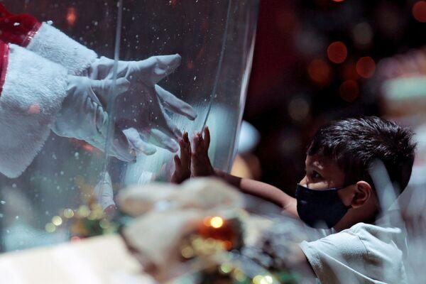 Un bambino comunica con il Babbo Natale attraverso uno schermo protettivo in un centro commerciale in Brasile, il 15 Dicembre 2020.  - Sputnik Italia