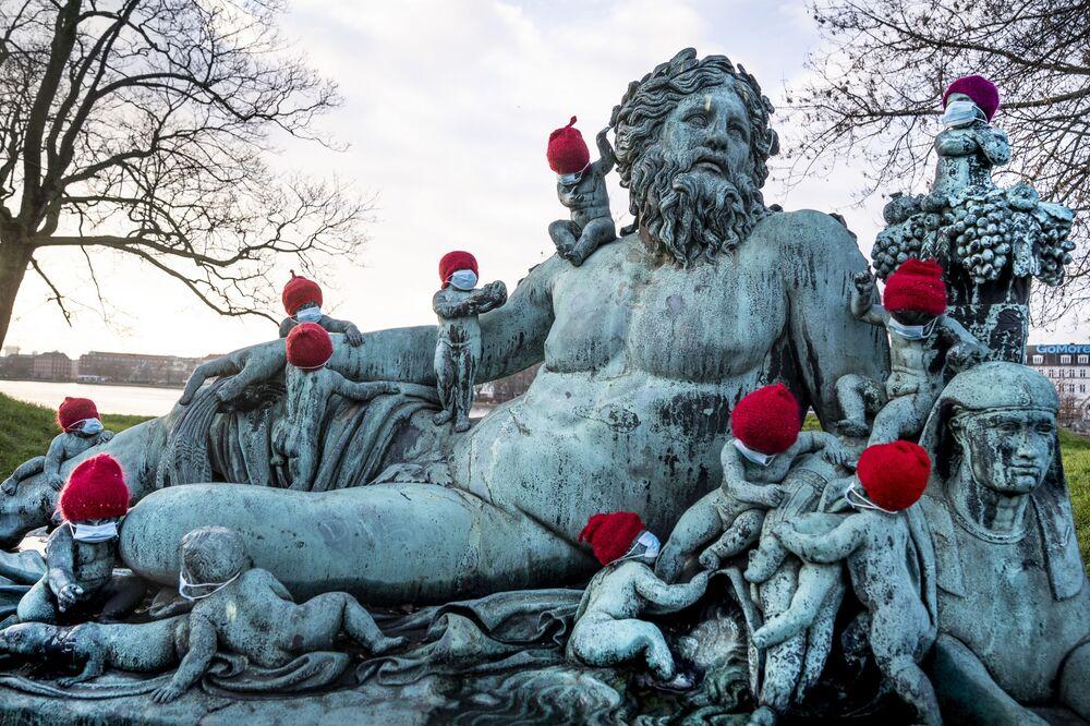 Piccole statue di bronzo in mascherina e cappellini natalizi a Copenaghen, Danimarca, il 16 Dicembre 2020.