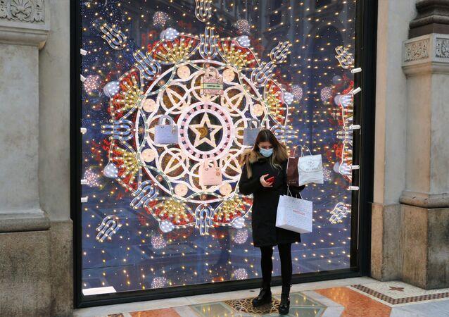Una donna in mascherina davanti a una vetrina di un negozio