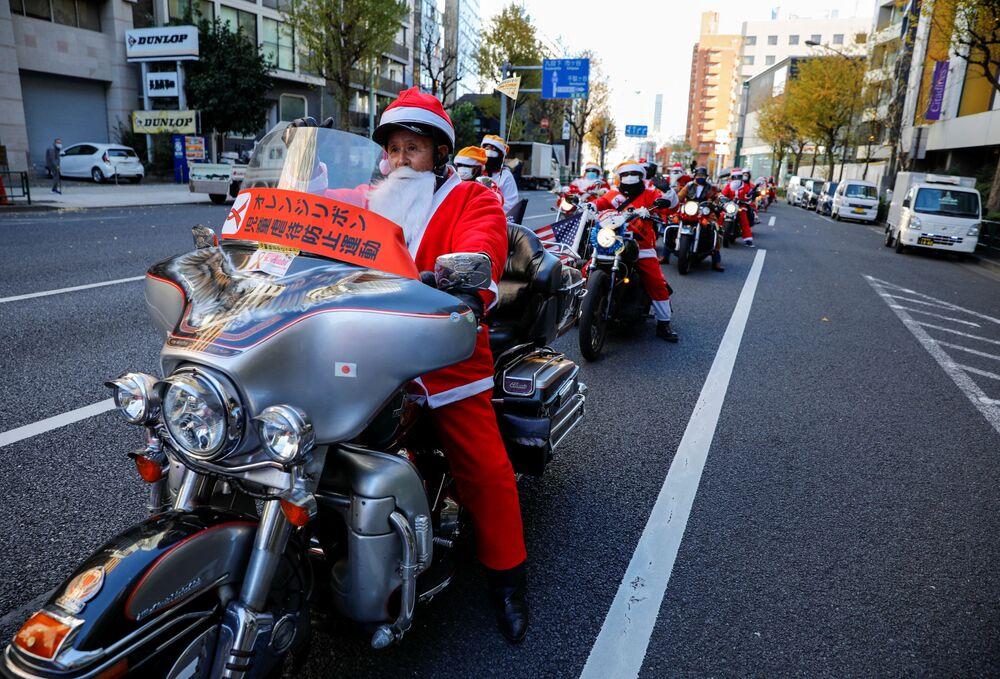 Le persone vestite da Babbo Natale in moto Harley Davidson durante la parata del Natale a Tokyo, Giappone.