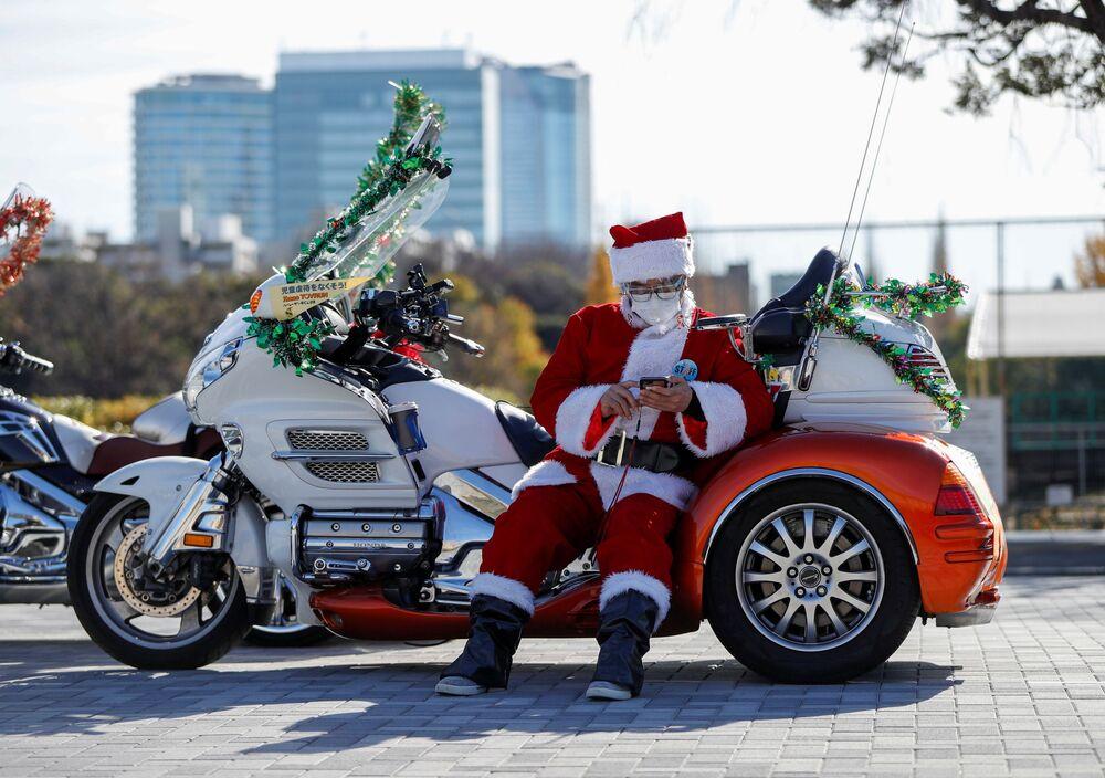 Un uomo vestito da Babbo Natale vicino alla moto Harley Davidson durante la parata del Natale a Tokyo, Giappone.