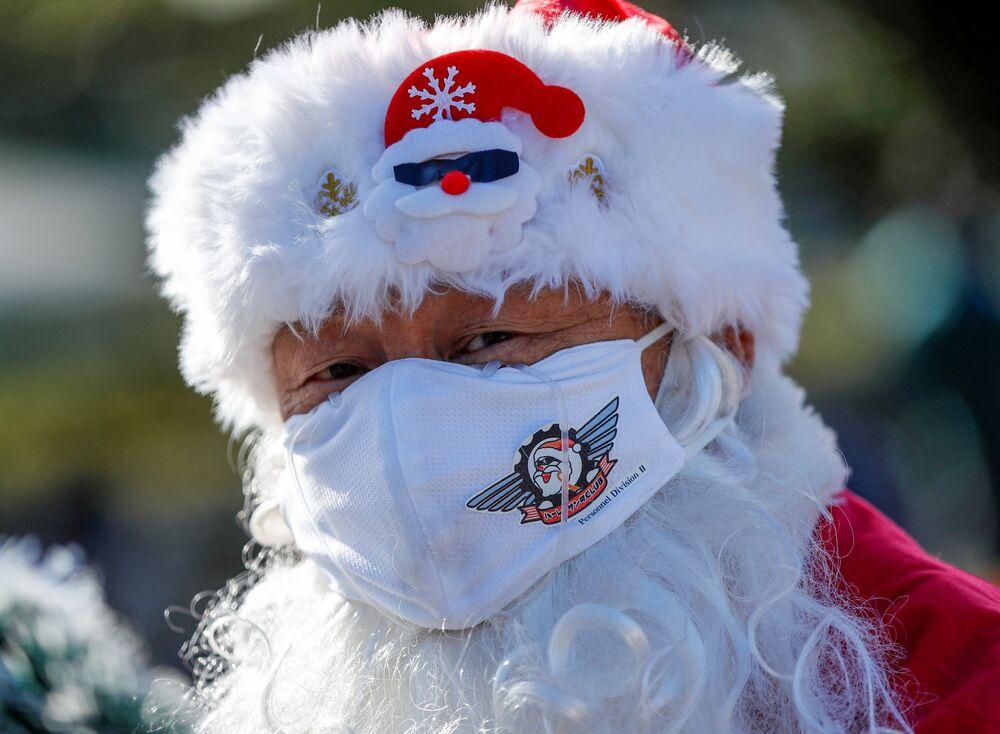 Un uomo in mascherina vestito da Babbo Natale durante la parata del Natale a Tokyo, Giappone.