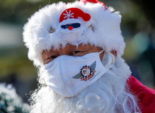Un uomo in mascherina vestito da Babbo Natale durante la parata del Natale a Tokyo, Giappone.  - Sputnik Italia