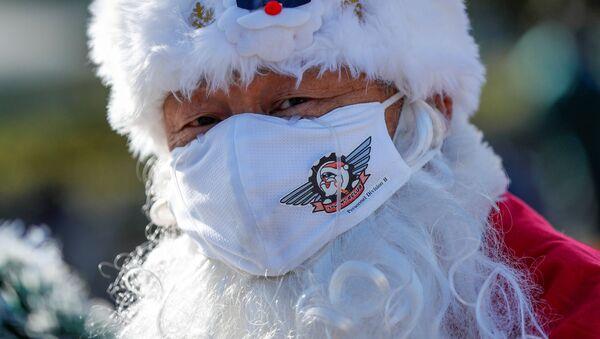 Un uomo con la mascherina ed il cappello da babbo natale - Sputnik Italia