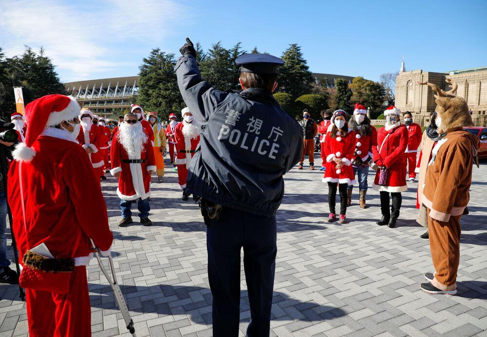 Un agente di polizia con i partecipanti della parata del Natale a Tokyo, Giappone.