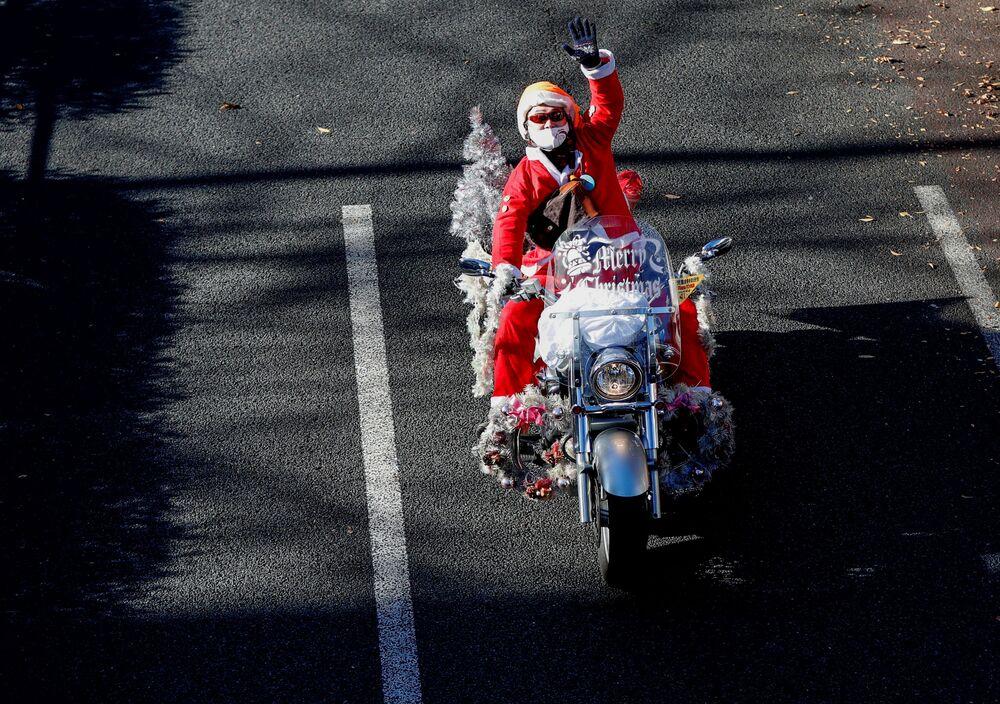 Un uomo vestito da Babbo Natale in moto Harley Davidson durante la parata del Natale a Tokyo, Giappone.