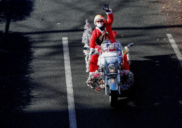 Un uomo vestito da Babbo Natale in moto Harley Davidson durante la parata del Natale a Tokyo, Giappone.  - Sputnik Italia