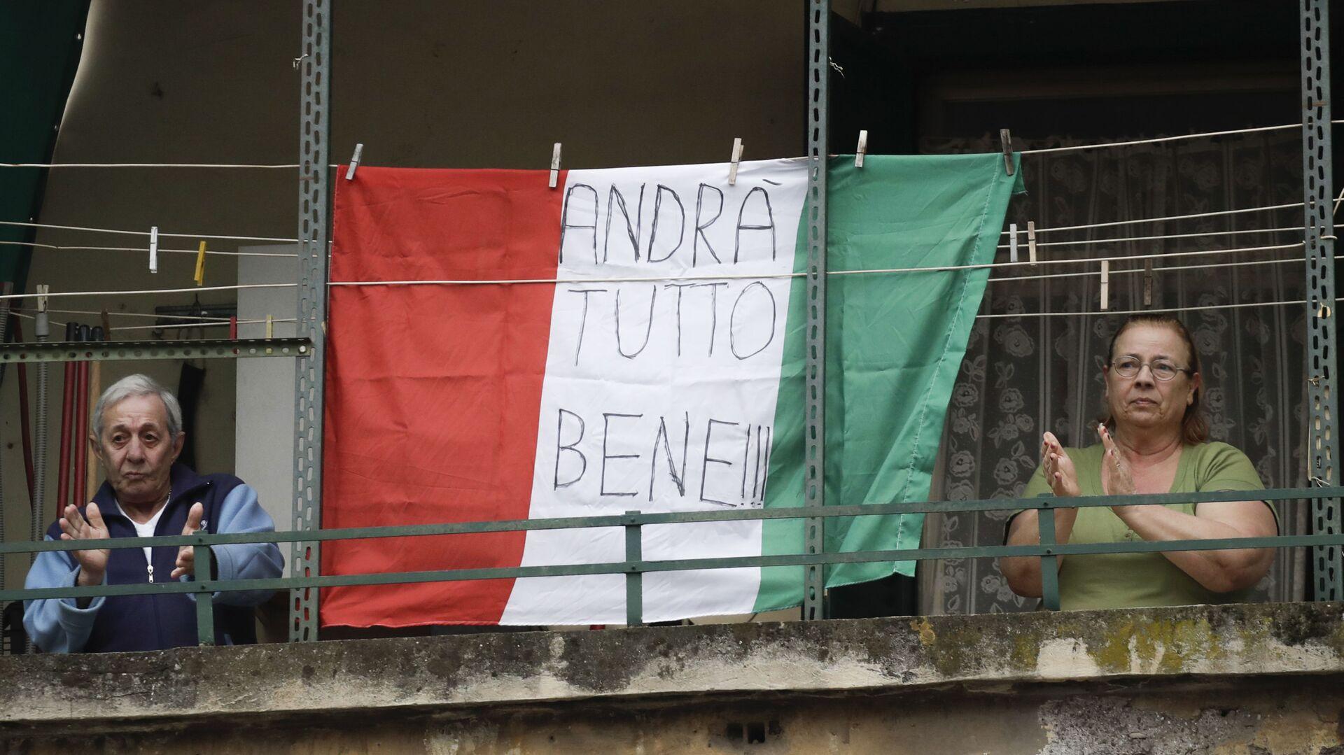 Coppia di anziani sul balcone con la bandiera dell'Italia con la scritta Andrà tutto bene a Roma - Sputnik Italia, 1920, 10.06.2021