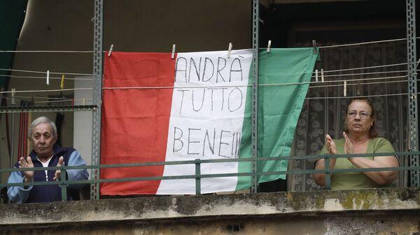 Coppia di anziani sul balcone con la bandiera dell'Italia con la scritta Andrà tutto bene a Roma - Sputnik Italia