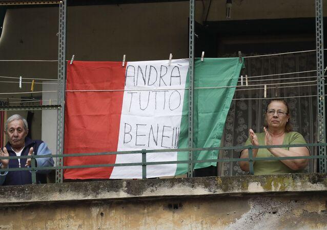 Coppia di anziani sul balcone con la bandiera dell'Italia con la scritta Andrà tutto bene a Roma