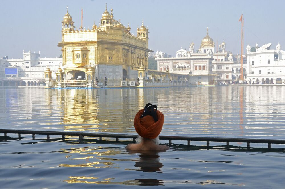 Un sikh fa il bagno nel un piccolo lago d'acqua, noto come il Sarovar, che circonda il Tempio d'Oro, India