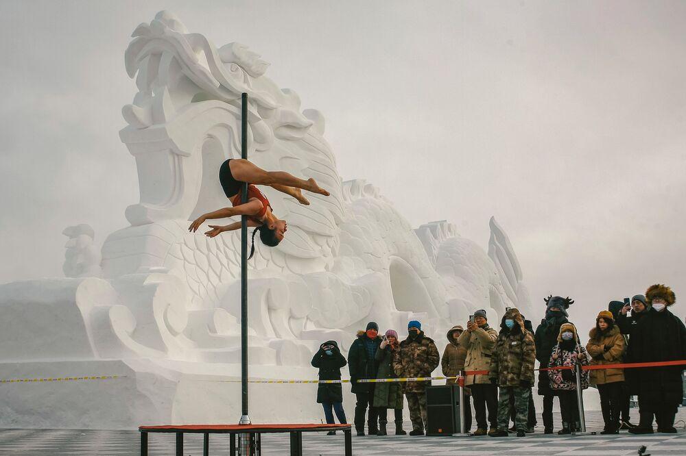 Questa foto scattata il 21 dicembre 2020 mostra le persone che guardano un artista durante una competizione di pole dance a Mohe, nella provincia di Henglongjiang della Cina nord-orientale