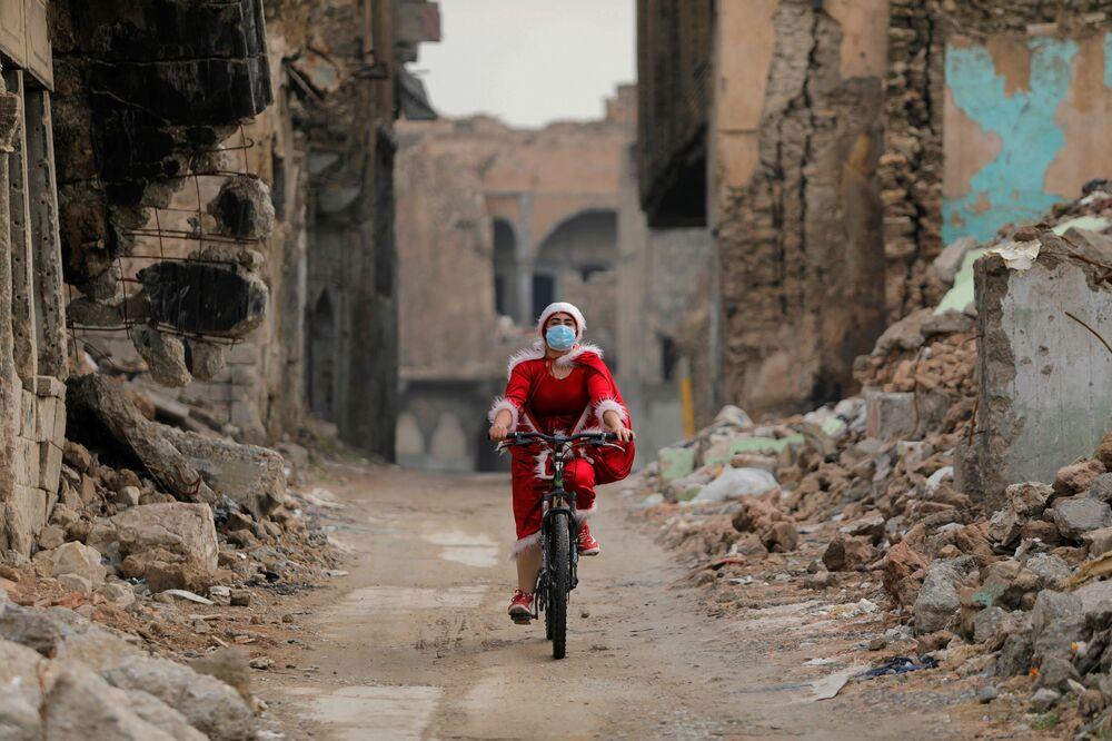 Una ragazza vestita da Babbo Natale per le strade di Mosul, in Iraq