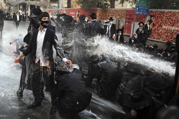 La polizia israeliana ha usato un cannone ad acqua contro uomini ebrei ultraortodossi che hanno bloccato la strada durante una manifestazione a Gerusalemme, martedì 22 dicembre 2020 - Sputnik Italia