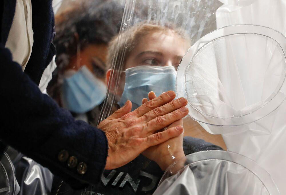 Un bambino ricoverato in ospedale con COVID-19 tocca la mano di suo padre in un reparto di un ospedale pediatrico a Roma, Italia