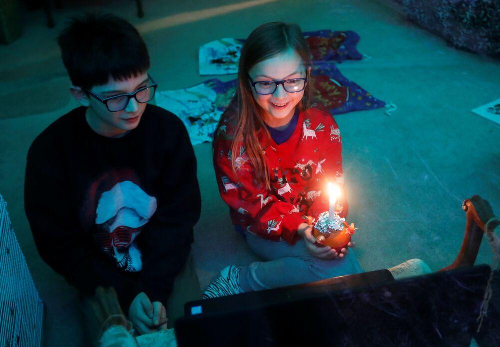 I bambini prendono parte alla messa online di Christingle alla vigilia di Natale, Blakesley, Northamptonshire, Gran Bretagna, il 24 Dicembre 2020.