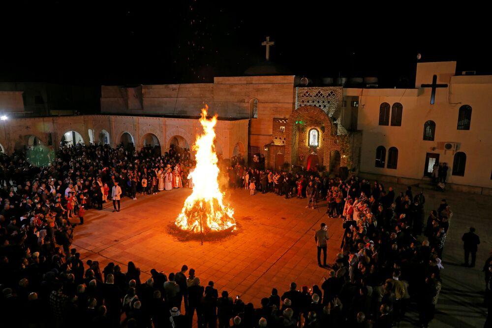 I fedeli vicino al fuoco durante la messa di Natale in Iraq nei pressi di Mosul, il 24 Dicembre 2020.