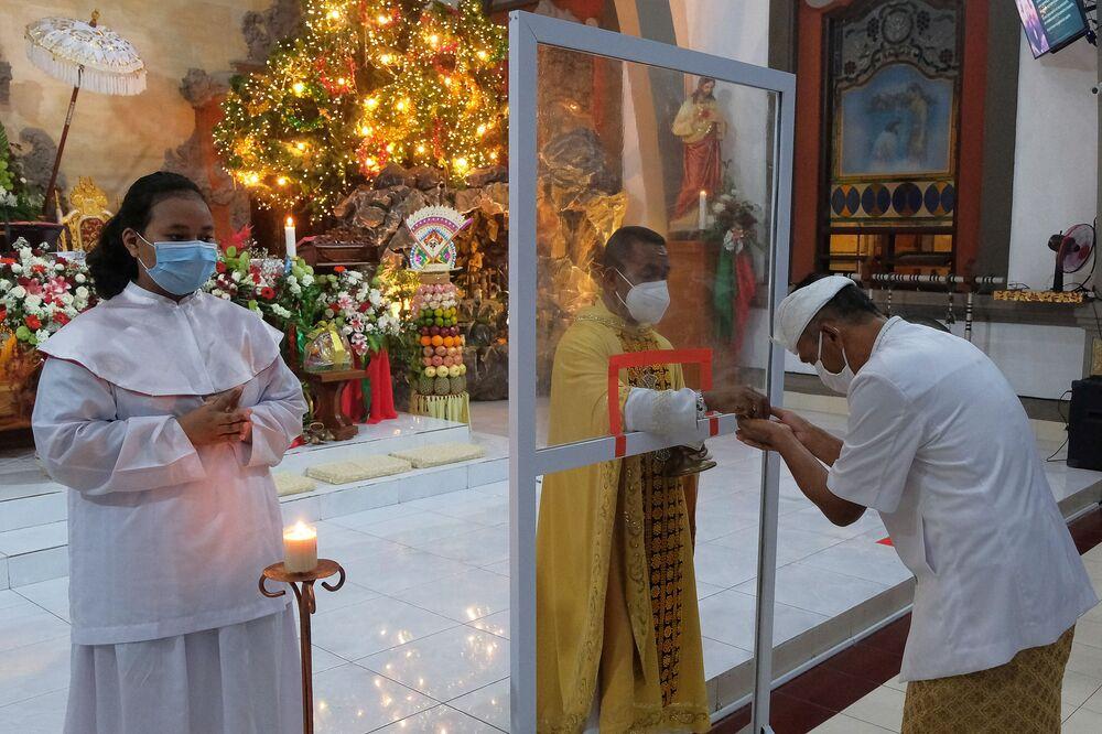 Le persone durante le celebrazioni natalizie in una chiesa a Badung, provincia di Bali, Indonesia, il 24 Dicembre 2020.