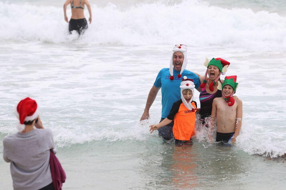 Le persone vestite con i costumi natalizi fanno le foto nel giorno di Natale sulla spiaggia di Bondi a Sydney, Australia, il 25 Dicembre 2020.