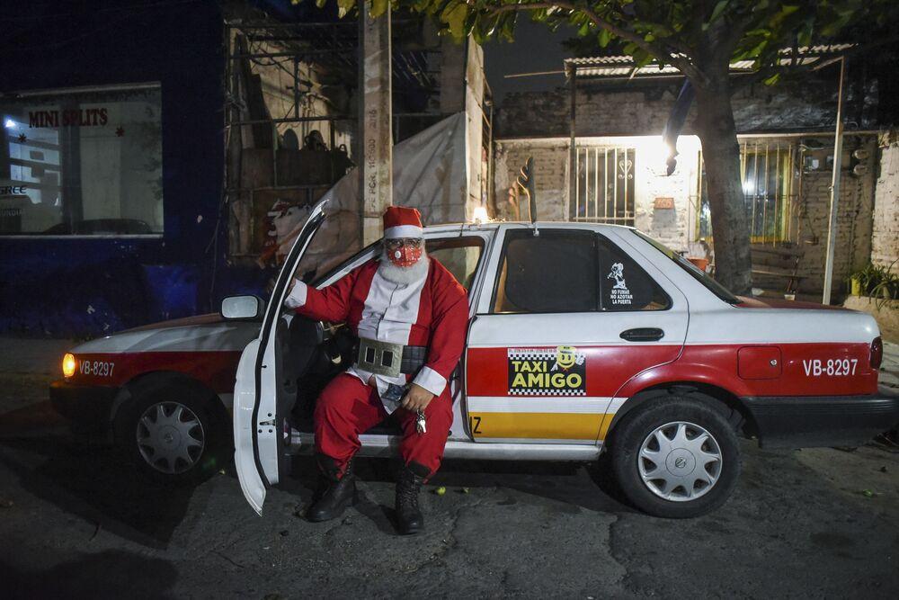 Un tassista vestito da Babbo Natale vicino alla sua macchina nella città messicana Boca del Rio, Messico, il 24 Dicembre 2020.