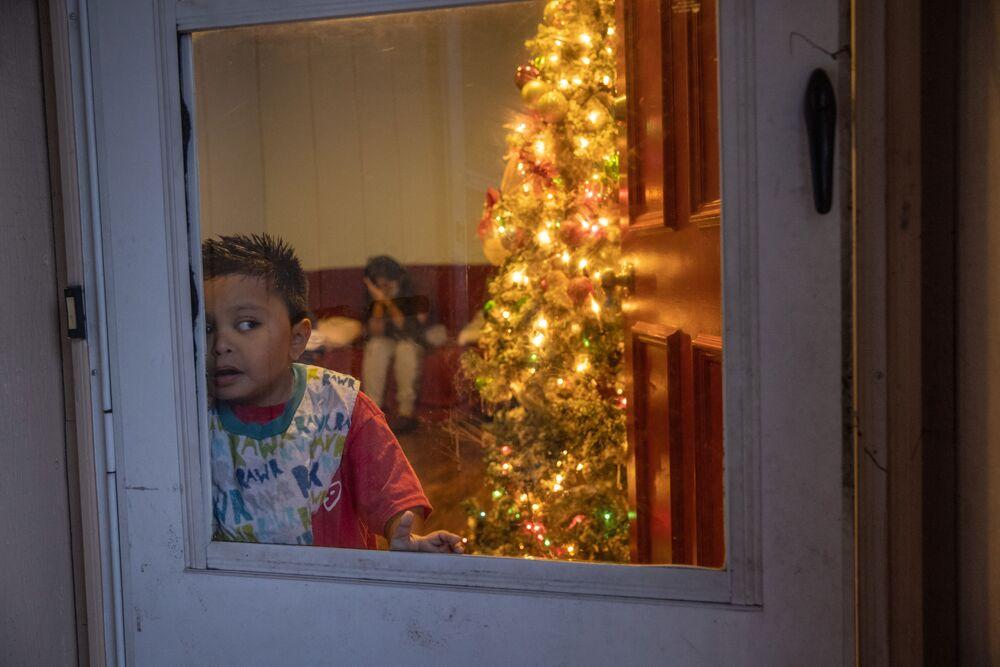 Un bambino di sette anni vicino all'albero di Natale a casa sua mentre tutta la sua famiglia è in ospedale a causa di Covid, Stamford, Connecticut, il 24 Dicembre 2020.