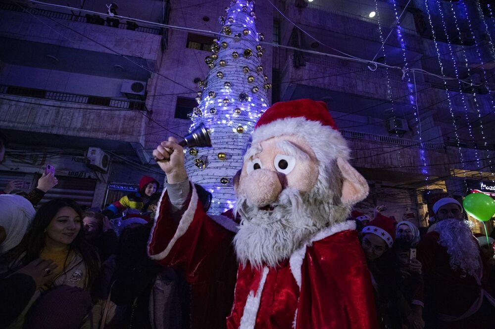 Un uomo vestito da Babbo Natale durante le celebrazioni nella città siriana Qamishli, Siria, il 24 Dicembre 2020.