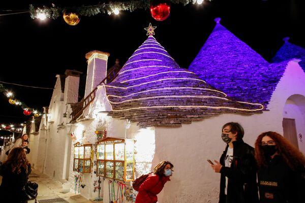 I turisti fanno un giro per Alberobello decorata con l'installazione di luci in occasione del Natale, Puglia, il 23 Dicembre 2020.  - Sputnik Italia