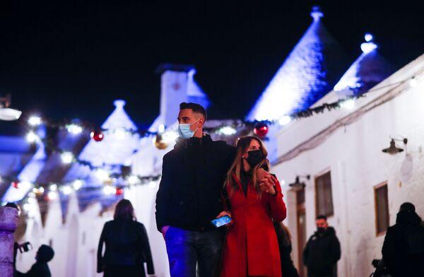 I turisti in mascherina fanno un giro per Alberobello decorata con l'installazione di luci in occasione del Natale, Puglia, il 23 Dicembre 2020.  - Sputnik Italia