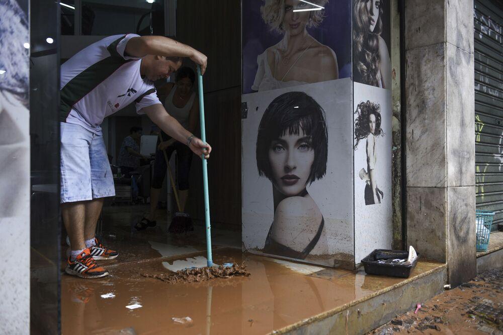 Un uomo pulisce il negozio dopo un'alluvione nella città brasiliana Belo Horizonte