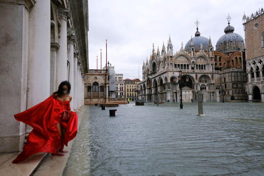 Una donna in Piazza San Marco allagata a Venezia, Italia