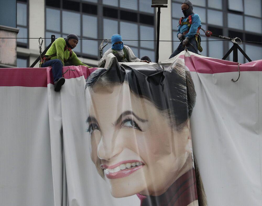 Gli operai piegano un cartellone pubblicitario per prepararsi al tifone Vongfong in arrivo, Filippine