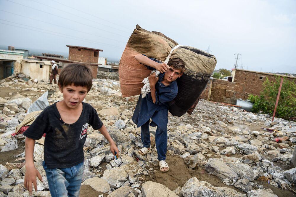 I giovani recuperano i resti delle cose dalle rovine delle case dopo un'alluvione improvvisa a Charikar, provincia di Parwan, Afghanistan