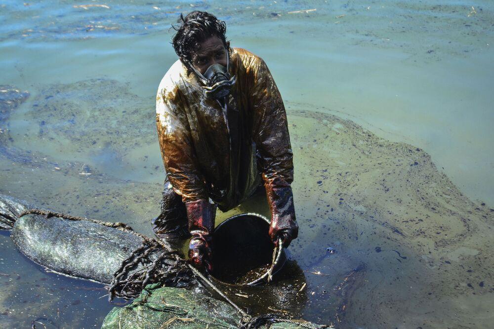Un uomo pulisce l'acqua dalla fuoriuscita di petrolio al largo delle Mauritius
