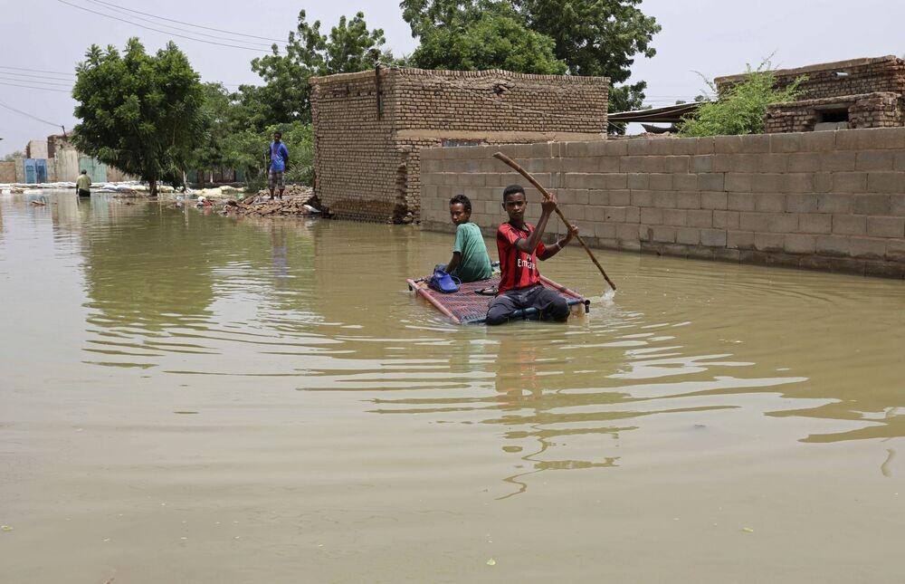 Giovani ragazzi percorrono una strada allagata su una zattera improvvisata nella città di Salmaniya, in Sudan