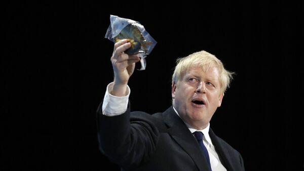 Il candidato alla leadership del partito conservatore Boris Johnson tiene in mano un pesce affumicato durante il suo discorso durante una riunione della leadership conservatrice all'ExCel Centre di Londra, mercoledì 17 luglio 2019 - Sputnik Italia