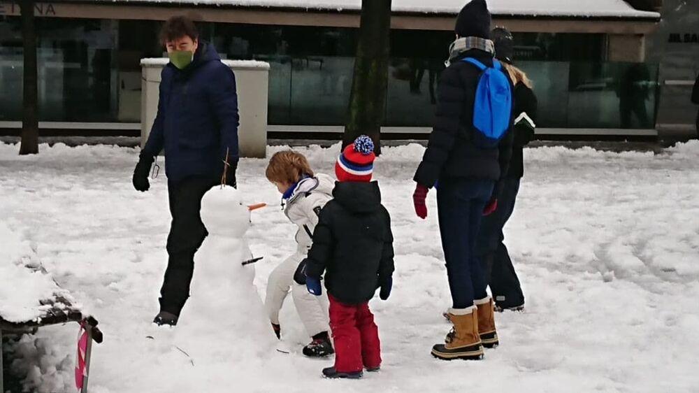 Milano sotto la neve, i bambini fanno un pupazzo di neve al parco