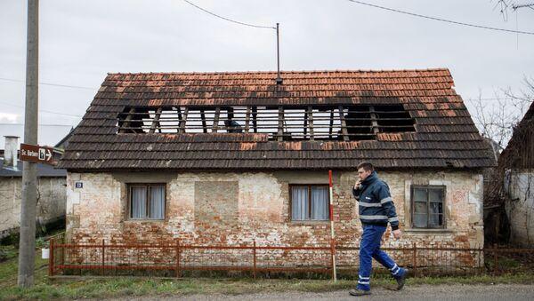 A man walks next to a damaged house after a 5.2 magnitude earthquake, in Brest Pokupski village, Croatia, December 28, 2020 - Sputnik Italia