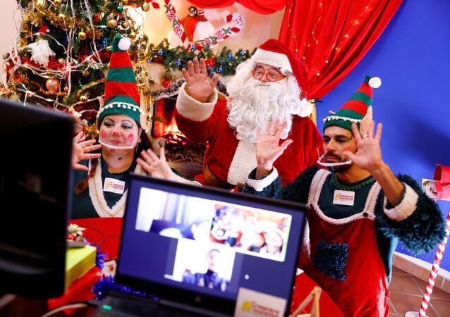 Un uomo vestito da Babbo Natale e i suoi assistenti vestiti da elfi chiacchierano con i bambini via Zoom a Roma, Italia