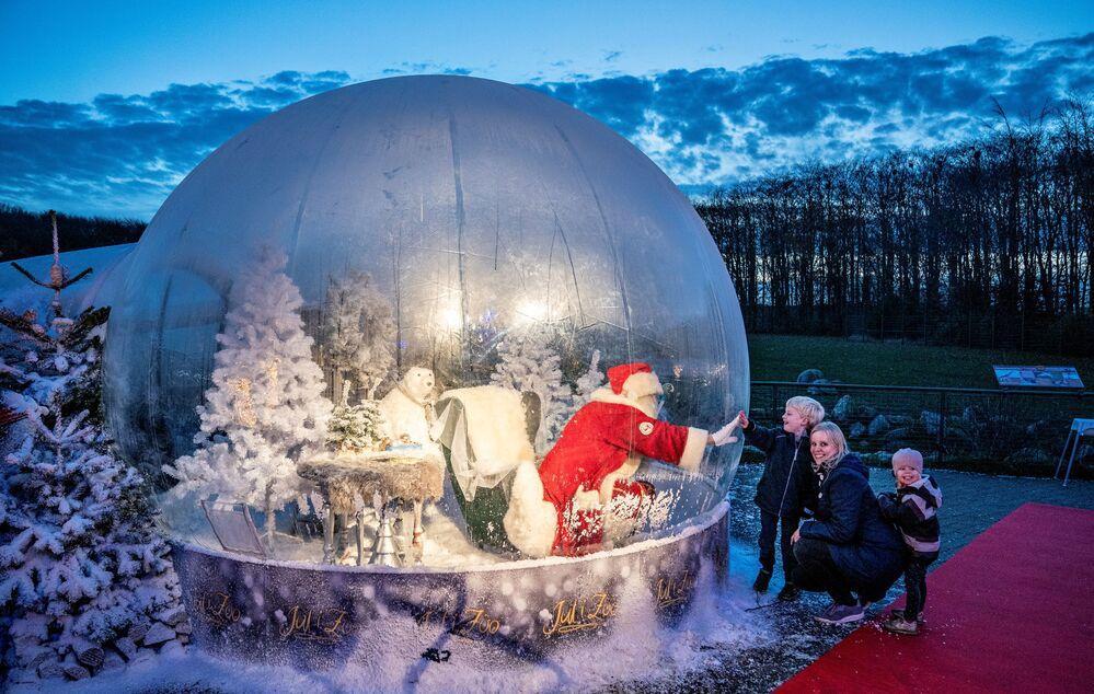 Un uomo vestito da Babbo Natale in una bolla trasparente incontra i bambini ad Aalborg, in Danimarca