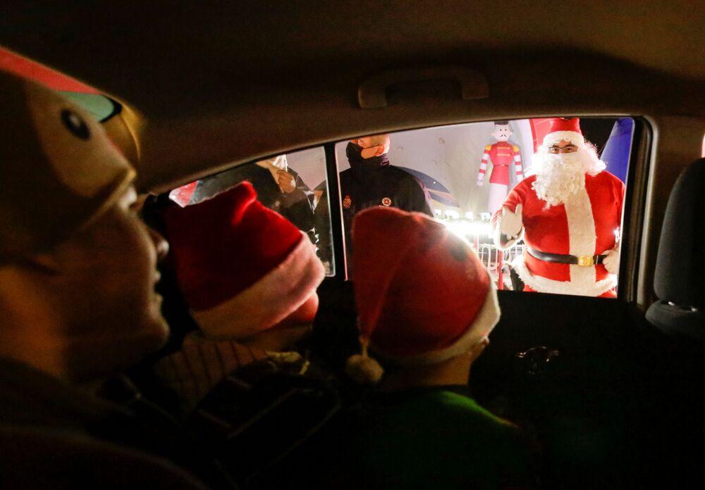 I bambini salutano un uomo vestito da Babbo Natale nella città messicana di Ciudad Juarez
