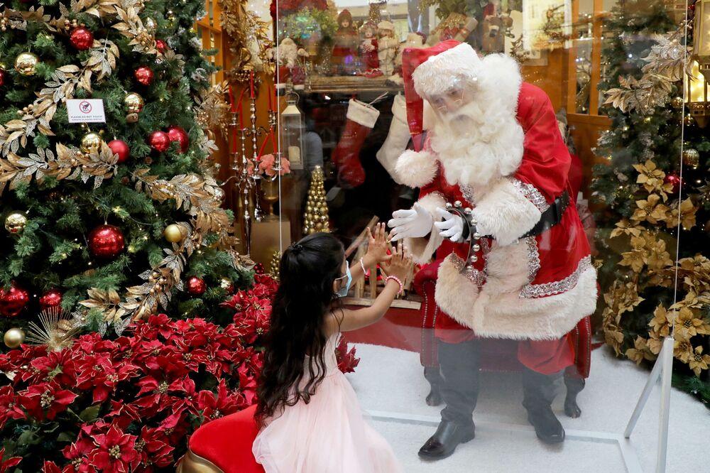 Un uomo vestito da Babbo Natale dietro un vetro protettivo in un centro commerciale a Kuala Lumpur, Malesia