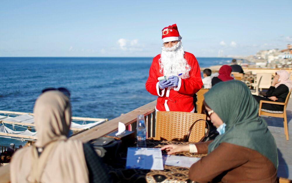 Un uomo palestinese vestito da Babbo Natale in un bar sulla spiaggia a Gaza