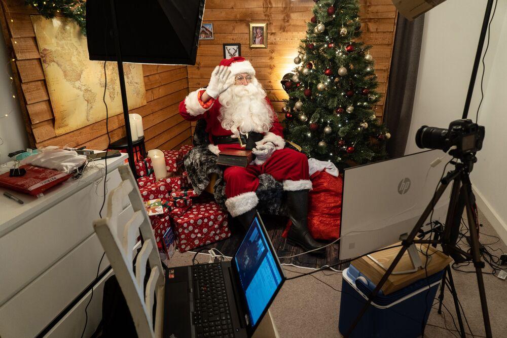 Uomo vestito da Babbo Natale parla con la sua famiglia via Zoom a Londra