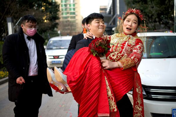 Lo sposo accompagna la sposa in hotel dopo il matrimonio avvenuto a Capodanno a Wuhan, in Cina, il 1 gennaio 2021.  - Sputnik Italia