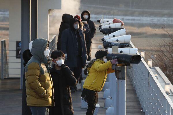 Le persone in mascherina guardano attraverso il binocolo nei pressi del confine tra le due Coree, il 1 gennaio 2021, Corea del Sud.  - Sputnik Italia