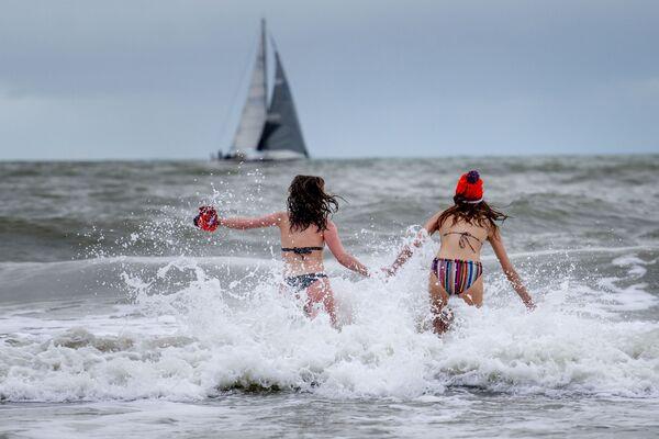 Le ragazze fanno il bagno nel mare a Scheveningen, Paesi Bassi, il 1 gennaio 2021.  - Sputnik Italia