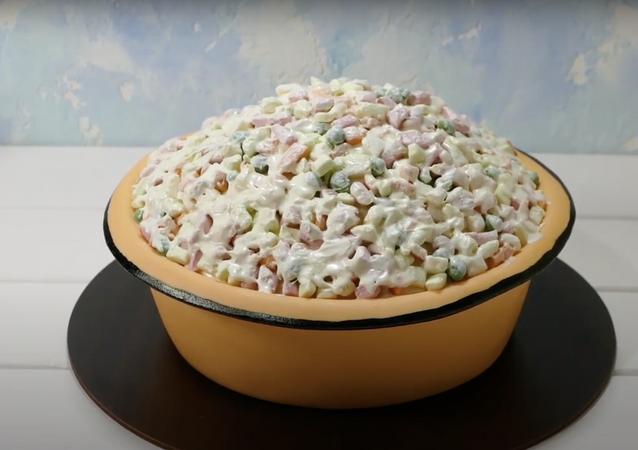 Una pasticcera ha preparato una torta a forma di insalata russa natalizia