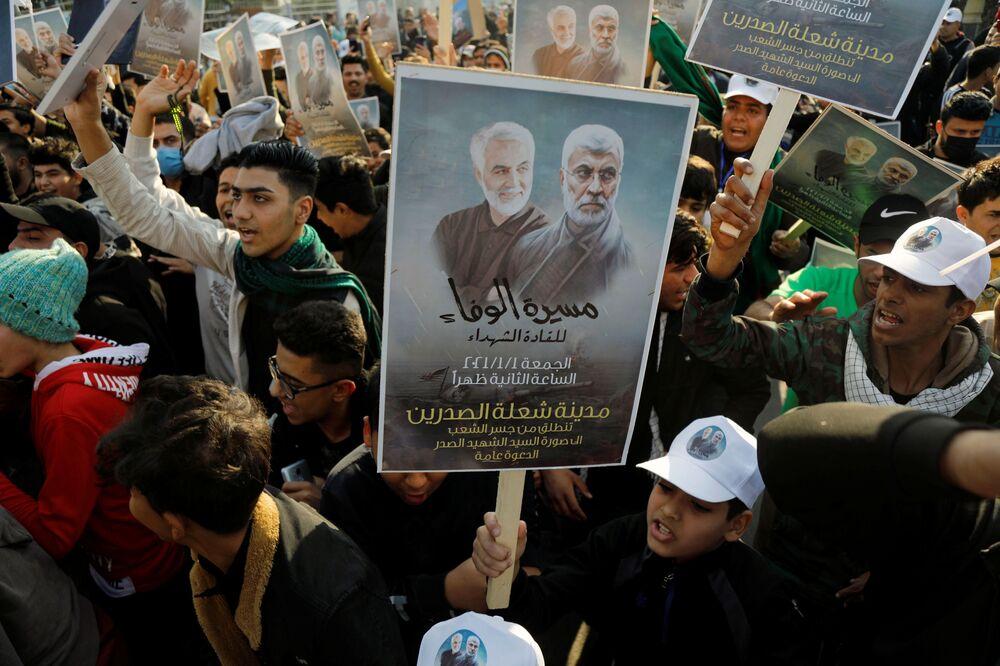 Persone con cartelli durante il primo anniversario della morte del comandante iraniano Qasem Soleimani e del comandante iracheno Abu Mahdi al-Muhandis a Baghdad